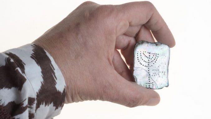 לוחית קטנה עשויה מאם הפנינה, שעליה חרותים מנורת שבעת קנים ומחתה