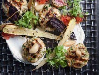 מורחים לאבנה על צלחת הגשה, מסדרים את קבב הדג ומעל ירקות צלויים