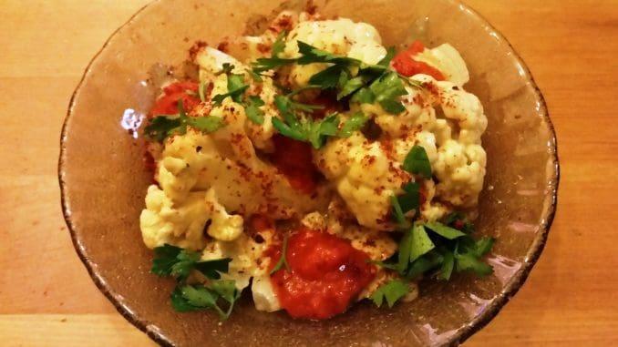 סיניה כרובית בטבון מוגשת עם טחינה עגבניות שרי, בצל ועשבים מהשוק