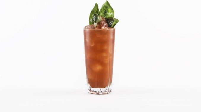 מקשטים את הכוס עם גבעול בזיליקום ופרוסת תות