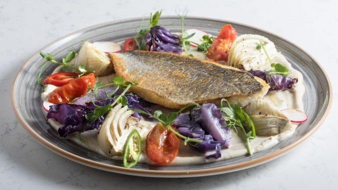 סי באס סינייה - פילה בס מונח על שכבה של טחינה יחד עם מגוון ירקות צלויים