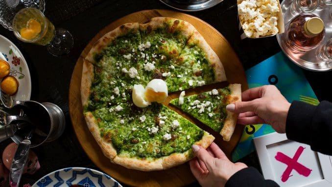 """""""פיצה ירוקה"""" משלבת פסטו עם מספר סוגים של גבינות וטוויסט של ביצה קשה. היא מהטובות בעיר הודות לבצק הדק והפריך ולרכיבים שהוסיפו מעליו. צילום דרור עינב"""