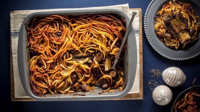 מניחים את חתיכות הבשר והבצלים על תבנית עם מעט ספגטי, מפזרים ערמונים ושופכים את שמן הבשר מעל ומכסים בשאר הספגטי. צילום אפיק גבאי