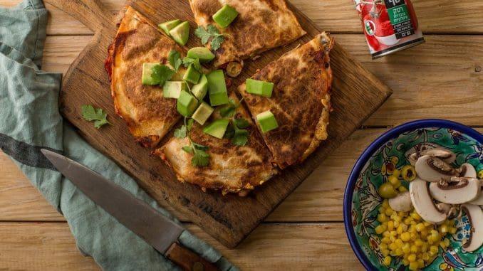מניחים טורטייה במחבת חמה. מורחים עליה את הרוטב ומפזרים גבינה ותוספות. צילום המערכת