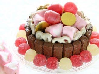 מדביקים ציפוי של וופלים כבסיס לעוגה כמו גדר וממלאים את החלק העליון בשלל ממתקים צבעוניים ומשמחים. צילום סטודיו כרמית