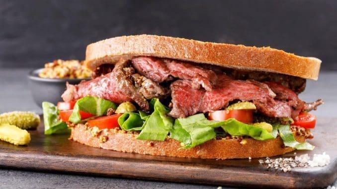 מורחים על פרוסת לחם חרדל ומניחים מעל את הבשר בשכבות. מסדרים מעל את פרוסות המלפפון החמוץ והעגבנייה. צילום אורן דאי. סטיילינג ענת לבל