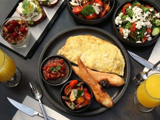 ארוחת בוקר סלווה כוללת אומלט תרד וגבינה בולגרית בליווי צזיקי וסלט שרי ובזיליקום טרי מוגש עם מקל פוקאצ'ה מהטאבון