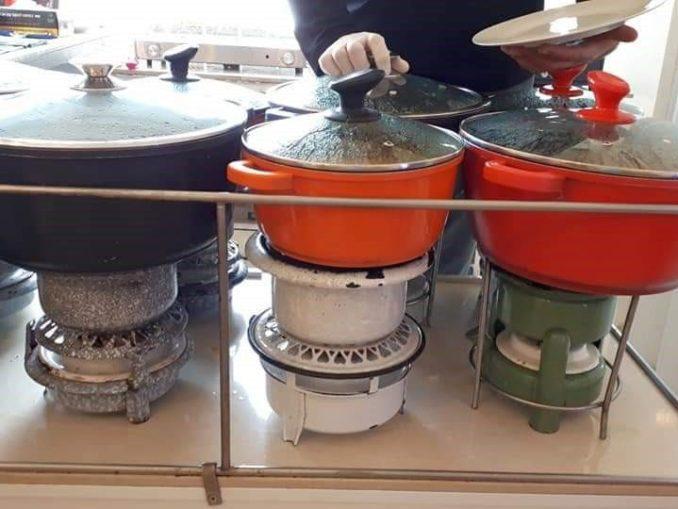 במרכז דלפק עם שמונה פתיליות ועליהן סירים גדולים ומבעבעים כשבאוויר ריח נהדר של אוכל ביתי. צילום איריס לוי