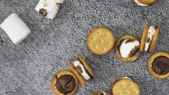 מסדרים בתבנית אפייה עם נייר פרגמנט קרקרים עגולים ומניחים מעל כל אחד מטבע שוקולד ועליו מרשמלו. צילום גלי איתן